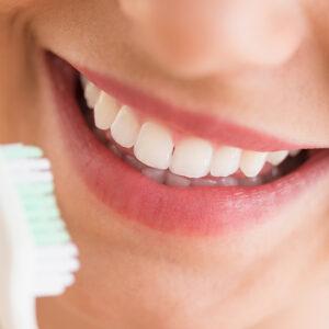 Uma boca sorrindo e uma escova de dente